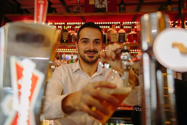 man smiling whilst pulling a pint of beer