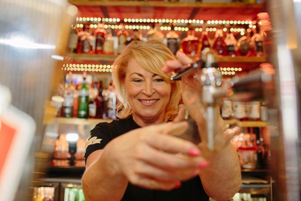 woman lifts up beer glass to a beer tap and starts pulling a pint of beer