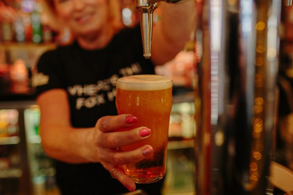 woman pulling a pint of ale from a tap