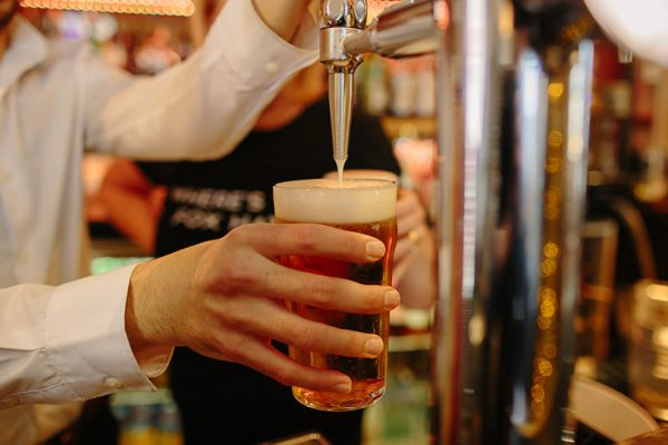 man pouring a pint of beer on tap in a pub