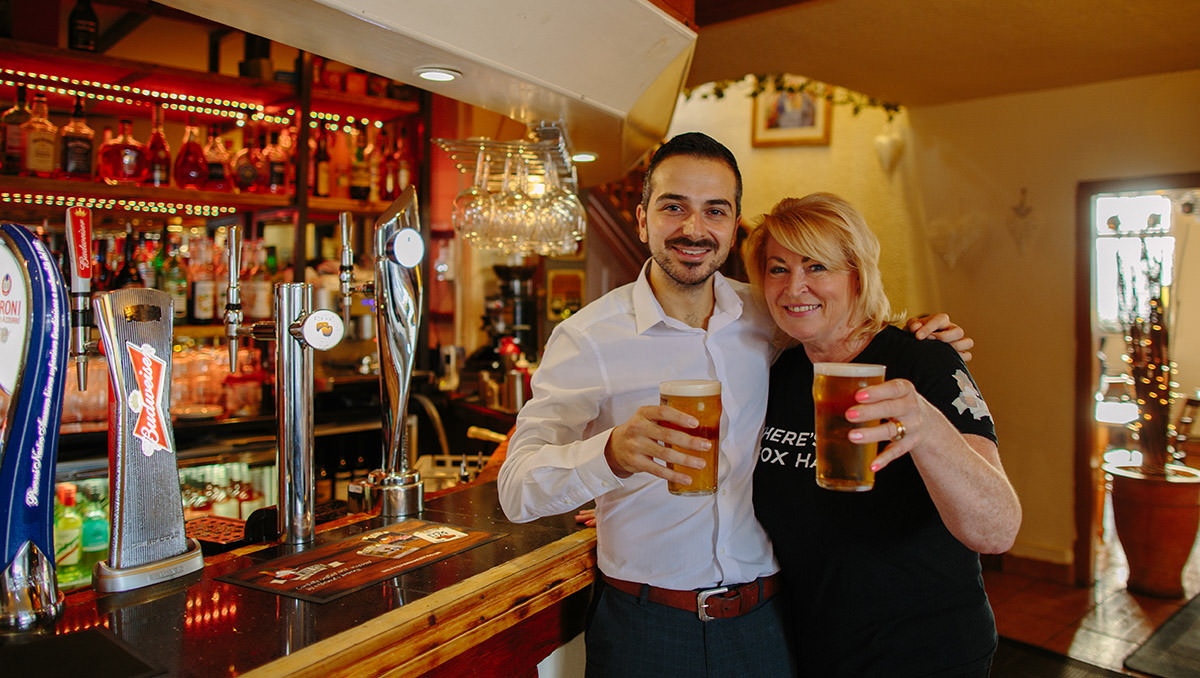 two people pose with pints of beer infront of a bar