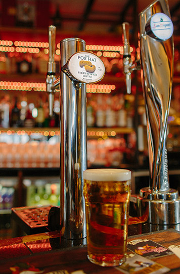 pint of golden ale sitting infrom of a beer tap