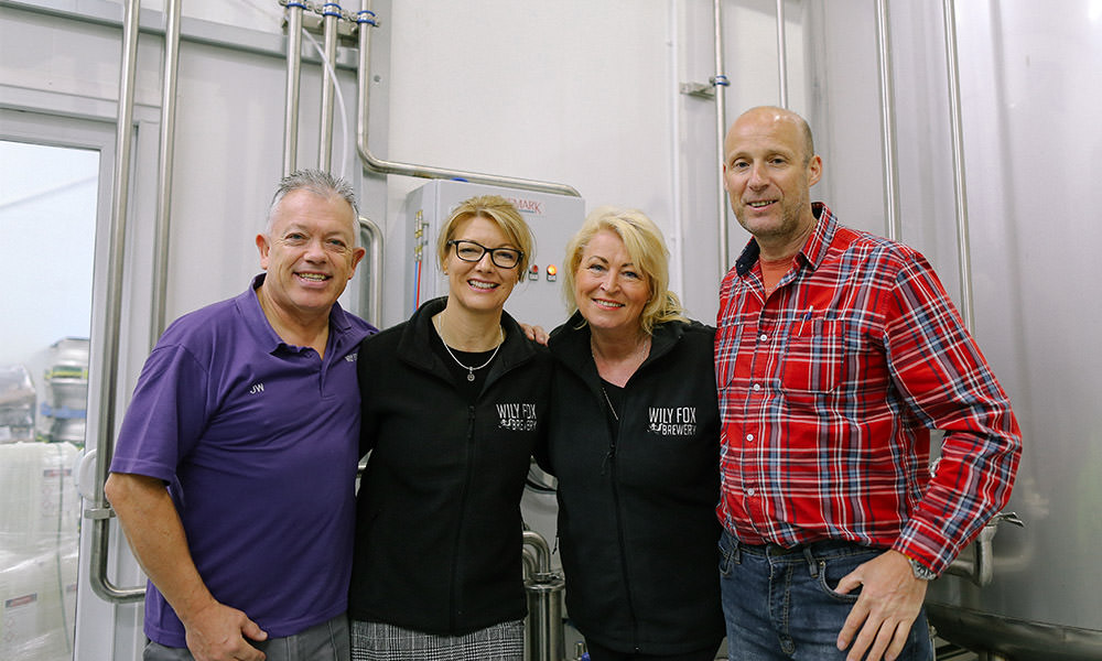 Dave joins the team with other team member smiling for a photograph inside a brewery