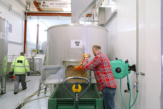wide view of a man working inside the wily fox brewery in wigan