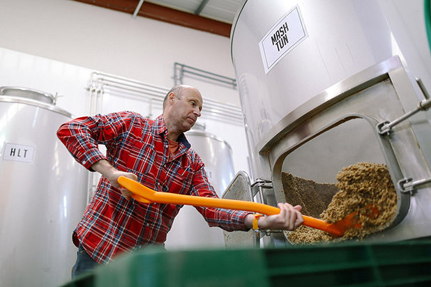 man empties the spent grain from mashing in