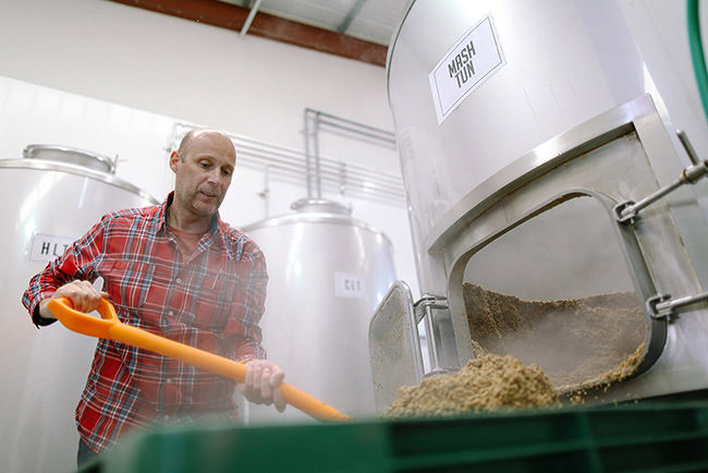 man emptying the spent grain from the mash tun
