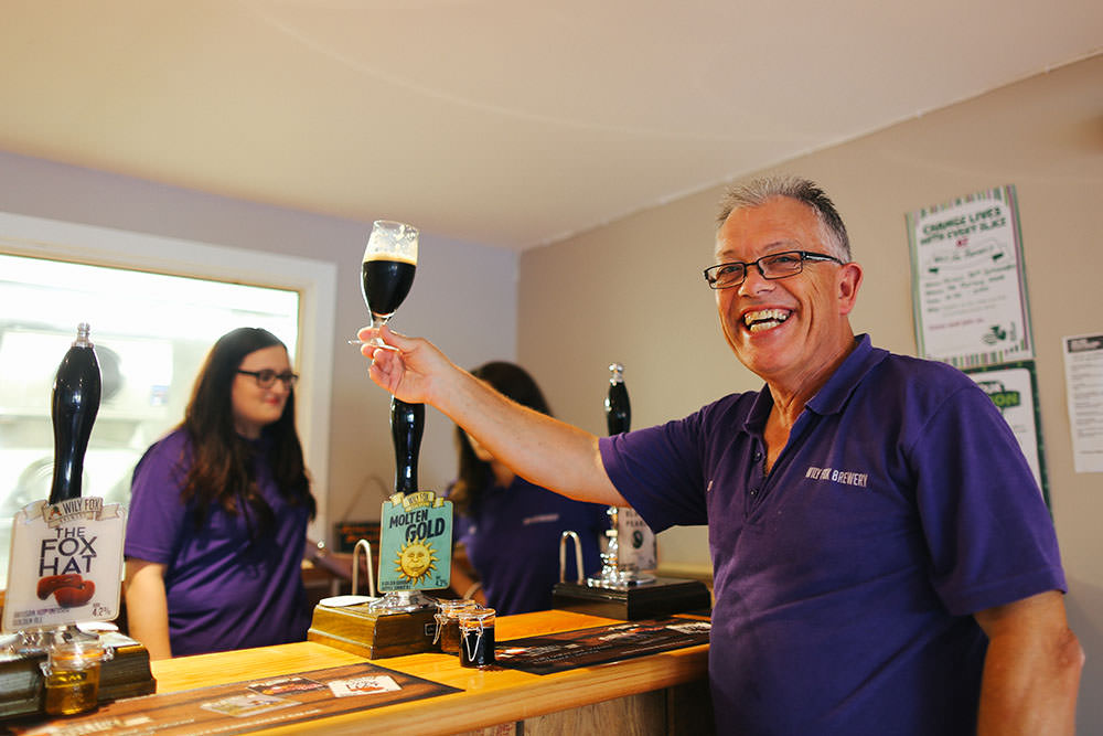man holds up a glass of dark beer in a bar with barmaids in the background