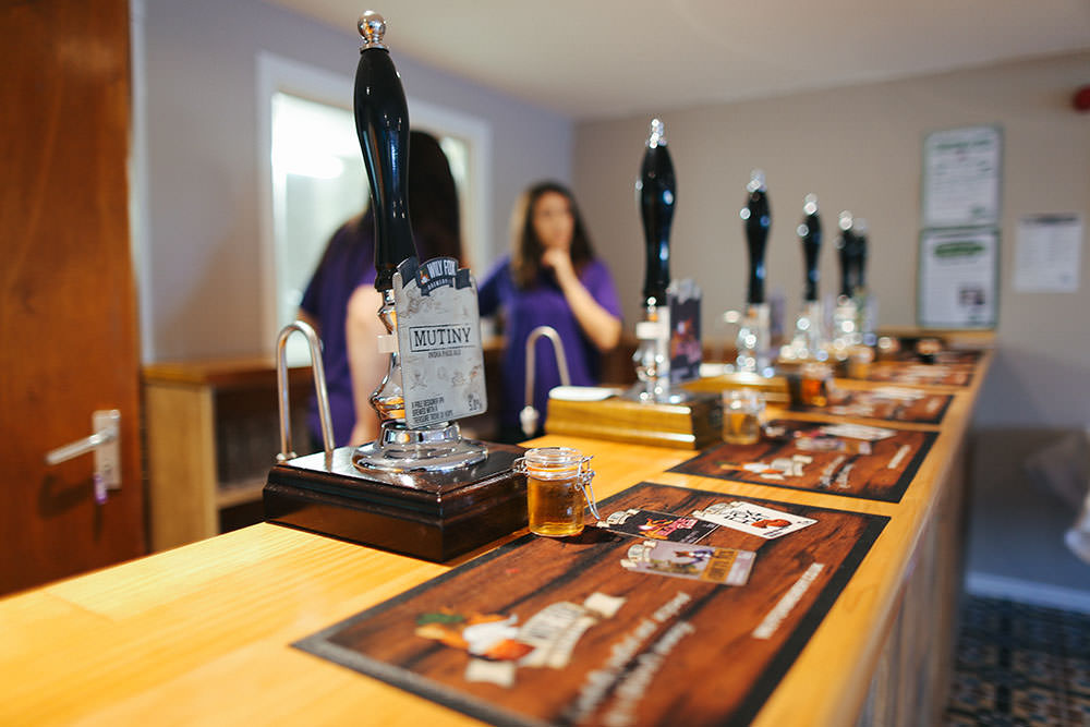 photo of a line of cask beer handpumps along a bar