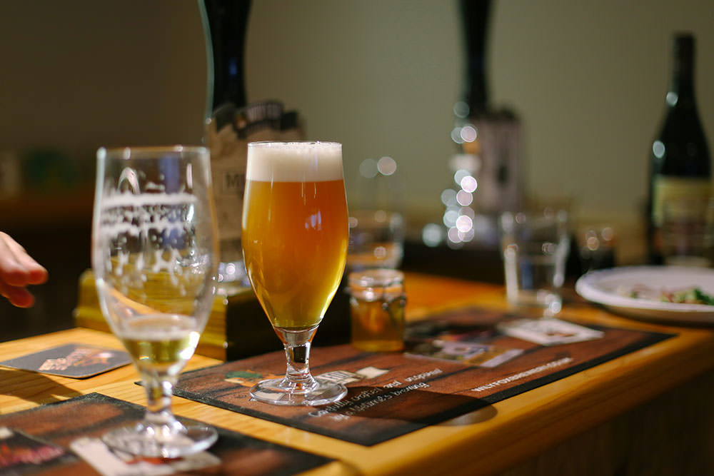 glass of cask ale settling on a bar in a brewery