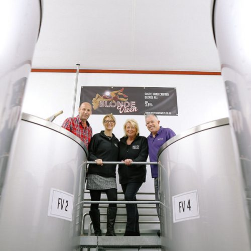 Brewery team pose for photo between brewing tank inside a brewery