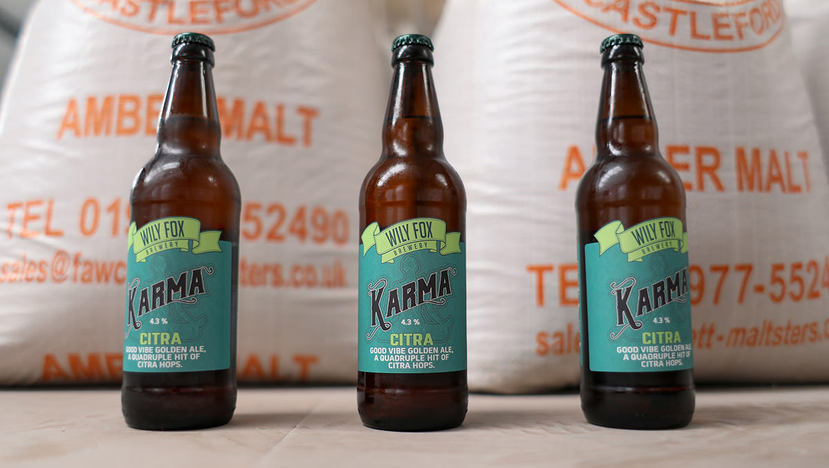 Wily Fox Karma Citra Bottle photos with bags of grain behind