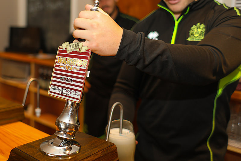 Rugby Player George Williams pulls a pint of the new Warrior IPA