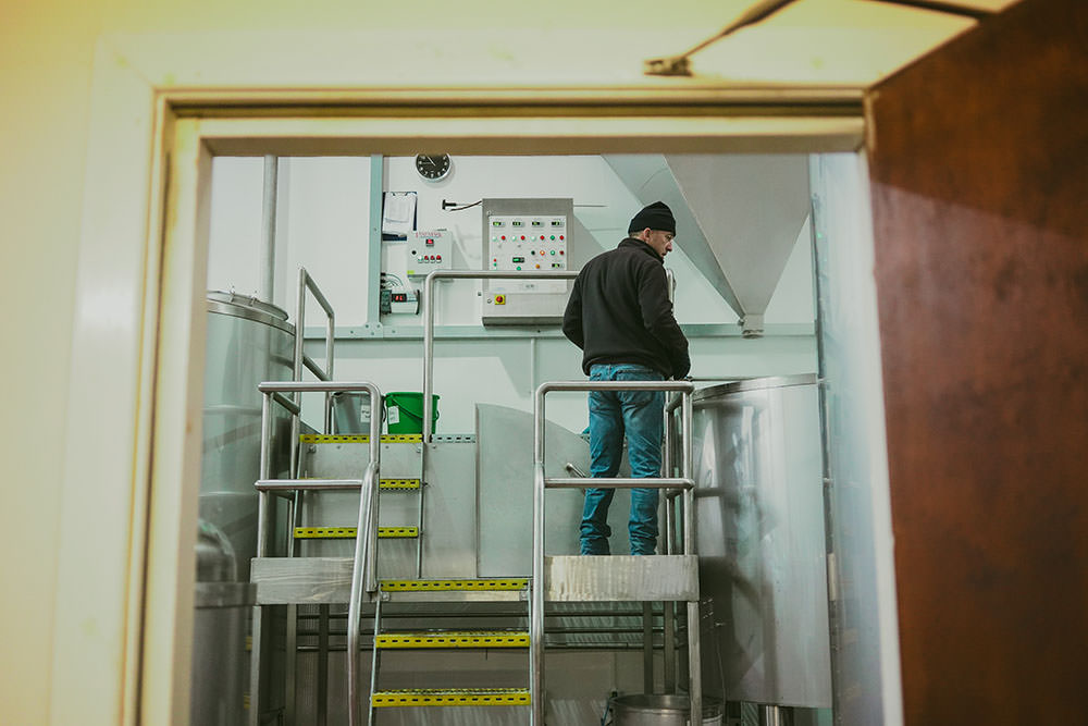 brewer oversees brewing of beer collaboration in brewery