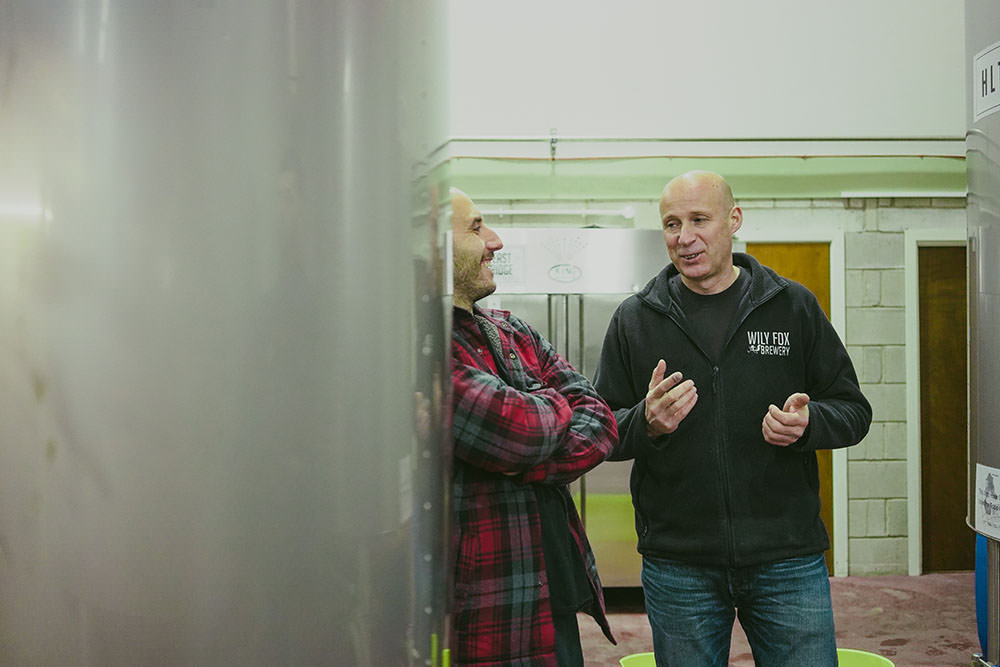 two men chat inside a brewery