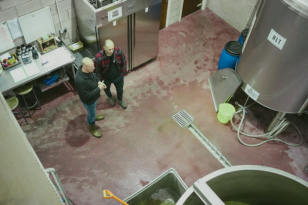men standing in a working brewery