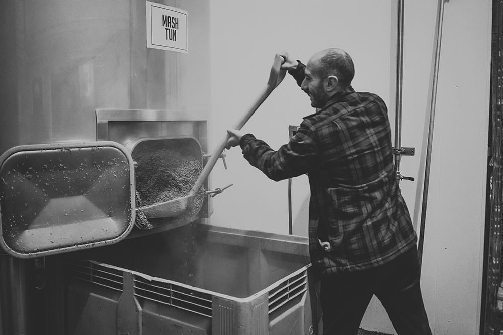 man emptying grain from the mash tun